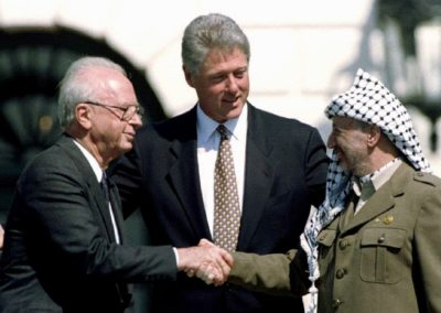 U.S. President Bill Clinton (C) looks on as Israeli Prime Minister Yitzhak Rabin (L) and Palestine Liberation Organization (PLO) leader Yasser Arafat shake hands after the signing of the Israeli-PLO peace accord at the White House in this September 13, 1993 file photo. REUTERS/Gary Hershorn